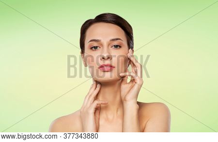 beauty, bodycare and people concept - beautiful young woman touching her face over lime green natural background