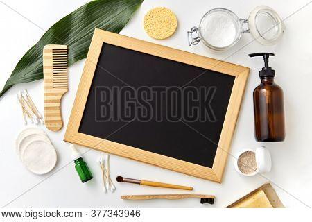 beauty, sustainability and eco living concept - natural cosmetics, bodycare eco products and chalkboard on white background