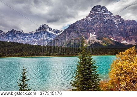 Fairytale Canada. The picturesque Lake Bow with emerald ice water. Snow-capped mountain peaks. Cloudy fall day in the Canadian Rockies. Concept of active, eco and photo tourism