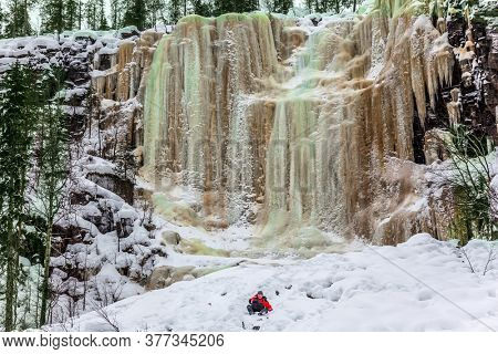 Happy hiker goes down in deep snow. Multicolored icicles of a frozen waterfall picturesquely fall off a steep cliff.  Lapland. The concept of photo and eco-tourism