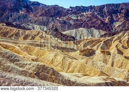 Picturesque multicolor sunset. California, USA, Zabriskie Point in Death Valley. Magnificent landscape and a variety of shades. The concept of active, extreme and photo tourism