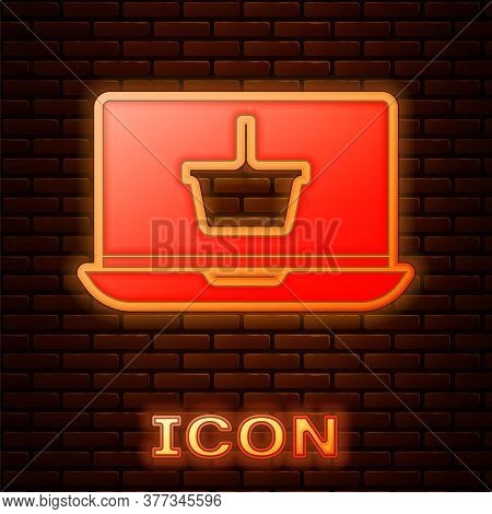 Glowing Neon Shopping Basket On Screen Laptop Icon Isolated On Brick Wall Background. Concept E-comm