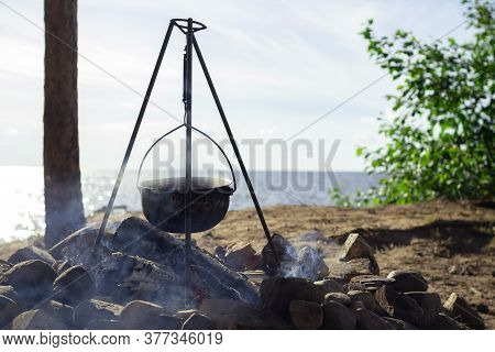Pot On The Fire By The Lake. Camping With A Pot Over A Burning Fire.