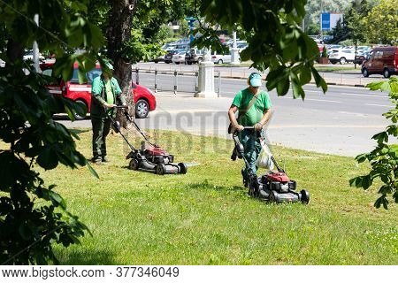 A Man Mows Grass In The City.