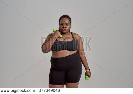 Plump, Plus Size African American Woman In Sportswear Holding Green Dumbbells, Posing In Studio Over