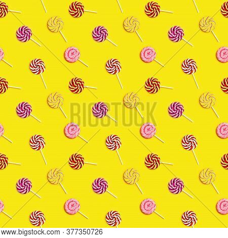 Seamless Pattern With Sweet Round Candy Lollypops With Stripes On Stick On Yellow Paper Background.