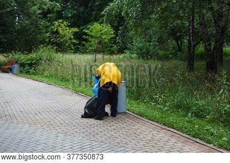 Man Sorting Garbage In Public Park. Trash Or Rubbish Gathering