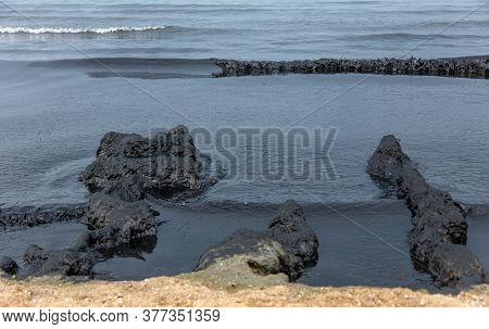 The Sea And The Beach Are Polluted With Oil. A Crude Oil Spill On The Sand Of A City Beach. Beach Oi