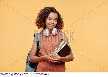 Portrait of smiling African-American student girl with headphones around neck holding books and satchel on back against bright background