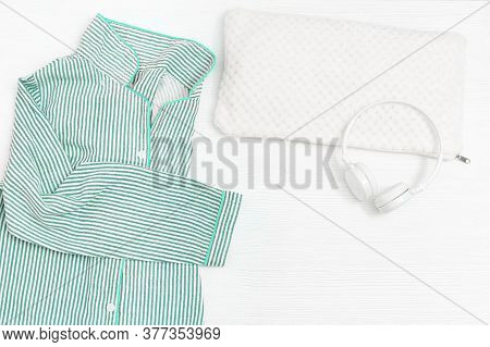 Comfort Neo-mint Color Pajama, Headphones, Fluffy Cushion On White Wooden Background. Accessories Fo