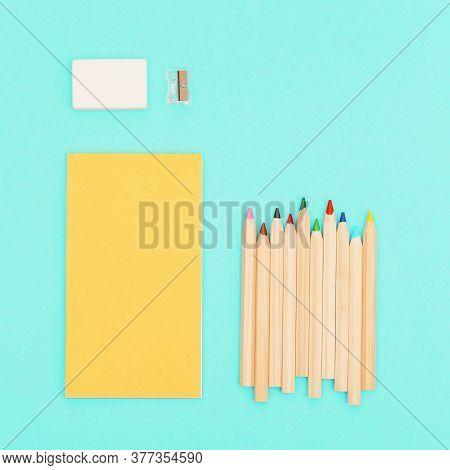 Top View Of Colored Pencils And Yellow Color Sketch Pad For Creativity. Set Of Wooden Multicolored P
