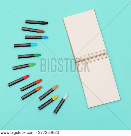 Top View Of Colored Pastel Crayons And Open Notebook On Spring For Drawing. Set Of Multicolored Chal