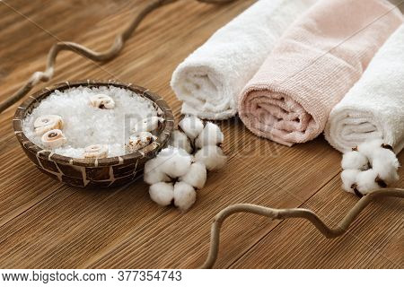 White Sea Salt In Bowl And Soft Fluffy Towel On Wooden Textured Surface. Spa Composition. Sea Salt F