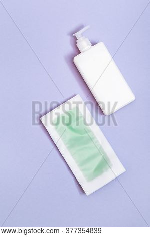 Set Of Female Of Hair Removal. Wax Strips, Body Moisturizer On Blue Paper Background With Copy Space