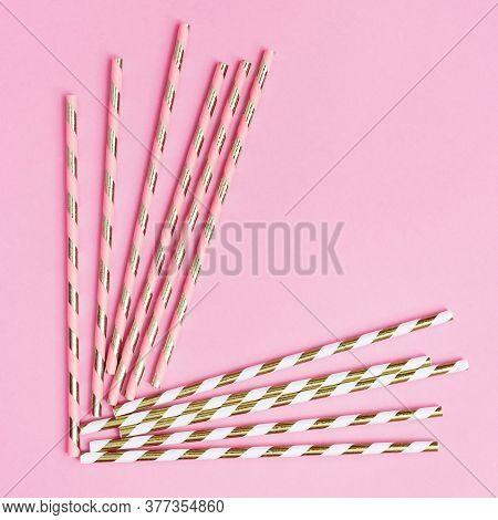 Bright Paper Drinking Straws With White And Golden Striped On Pink Background With Copy Space. Conce