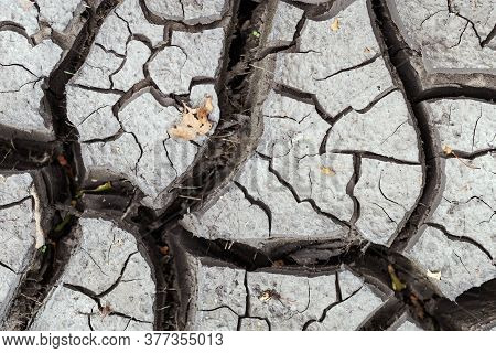 Black Earth With Cracks. Soil Texture Background.