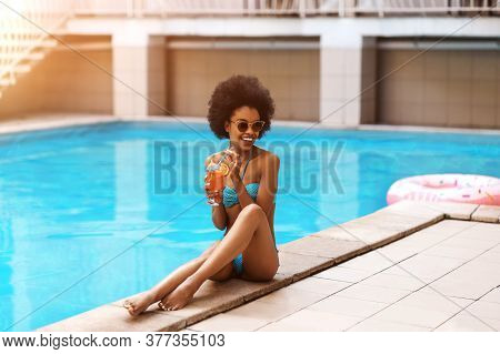 Happy African American Lady In Bright Swimsuit Enjoying Her Cocktail Drink At Poolside On Hot Summer