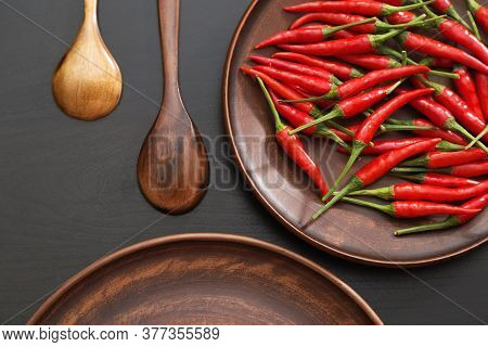 Hot Red Chili Peppers In A Brown Earthenware Dish On A Wooden Table. Top View And Copyspace For Text