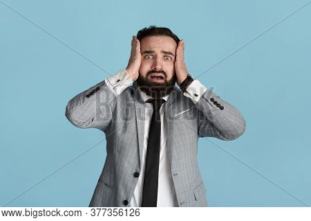 Frightened Corporate Employee Grasping His Head In Terror On Blue Background