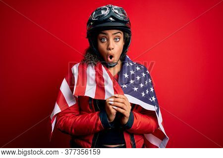 African american patriotic motorcyclist girl wearing moto helmet wearing united states flag scared in shock with a surprise face, afraid and excited with fear expression