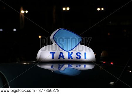 Taxi Light Sign Or Cab Sign In Blue And White Color On The Car Roof At The Street In The Dark Night,