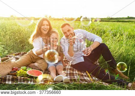 Picnic Family Fun. Adorable Girl With Her Mom And Dad Blowing Soap Bubbles In Coutryside On Summer D