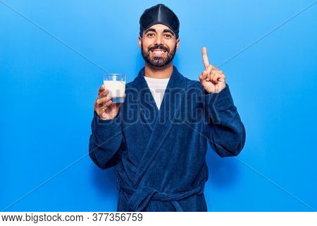 Young hispanic man wearing sleep mask and robe drinking milk smiling with an idea or question pointing finger with happy face, number one