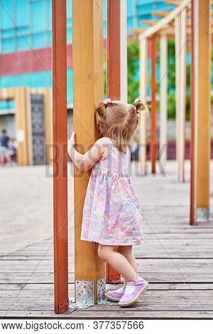 A Little Girl With Two Tails Plays Hide And Seek On The Playground