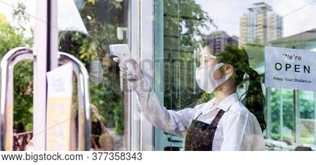 Asian waitress with face mask take temperature to customer before getting in restaurant. Restaurant New normal restaurant lifestyle concept after coronavirus covid-19 pandemic.