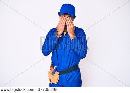 Handsome young man with curly hair and bear weaing handyman uniform rubbing eyes for fatigue and headache, sleepy and tired expression. vision problem