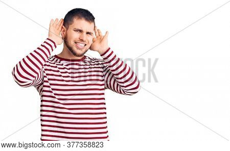 Young handsome man wearing striped sweater trying to hear both hands on ear gesture, curious for gossip. hearing problem, deaf