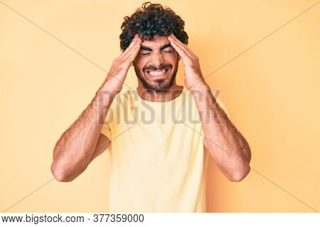 Handsome young man with curly hair and bear wearing casual tshirt over yellow background with hand on head, headache because stress. suffering migraine.