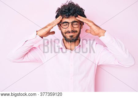 Handsome young man with curly hair and bear wearing business shirt and glasses suffering from headache desperate and stressed because pain and migraine. hands on head.