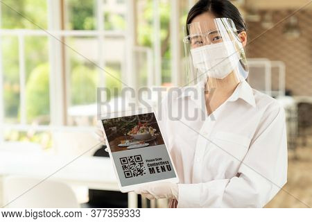 Asian waitress with face mask and face shield hold digital tablet with QR code for customer to scan for online contactless menu. QR code lead to text
