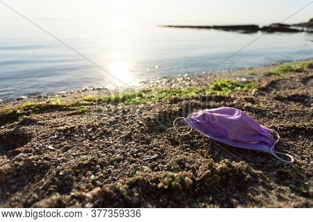 Ocean Pollution. Wasted Medical Mask Lying On Polluted Beach Outdoors. Ecological Background With Fr