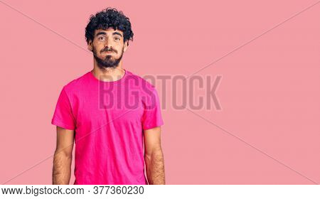 Handsome young man with curly hair and bear wearing casual pink tshirt puffing cheeks with funny face. mouth inflated with air, crazy expression.