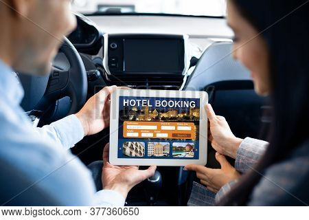 Couple Booking Hotel On Digital Tablet Sitting In Car Going On Vacation Or Business Trip. Travel Acc