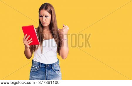 Young beautiful hispanic woman holding touchpad annoyed and frustrated shouting with anger, yelling crazy with anger and hand raised