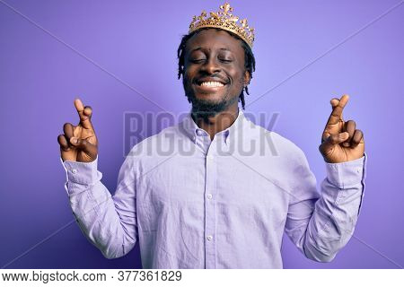 Young african american man wearing golden crown of king over isolated purple background gesturing finger crossed smiling with hope and eyes closed. Luck and superstitious concept.