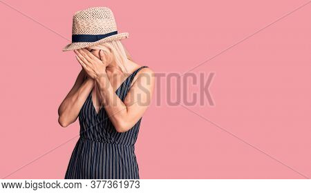 Young beautiful blonde woman wearing summer hat and dress with sad expression covering face with hands while crying. depression concept.
