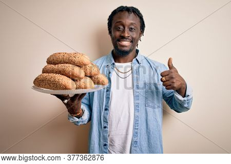 Young african american man holding tray with healthy wholemeal bread over white background happy with big smile doing ok sign, thumb up with fingers, excellent sign