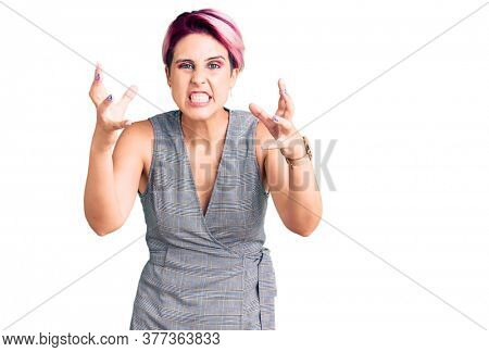 Young beautiful woman with pink hair wearing casual clothes shouting frustrated with rage, hands trying to strangle, yelling mad