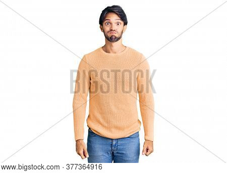 Handsome hispanic man wearing casual sweater puffing cheeks with funny face. mouth inflated with air, crazy expression.