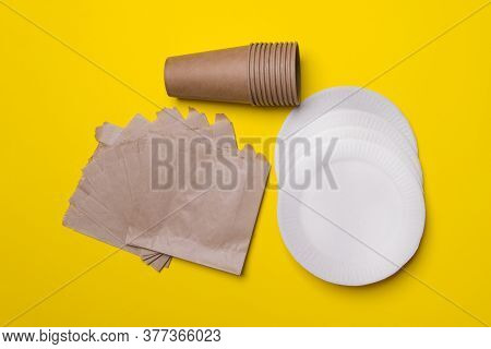 Eco-friendly Kitchen Ware, Plate, Cup, Bag, In Yellow Colored Paper Background. Top View. Close-up.