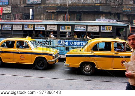 Kolkata, India: Yellow Taxi Cabs Driving On Busy Streets With Pedestrians And Busses On January 19,