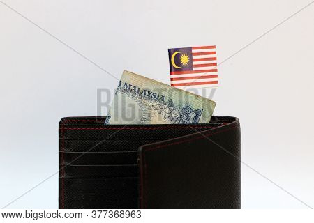 One Ringgit Banknote Of Malaysia And Mini Malaysian Nation Flag Stick On The Black Wallet With White