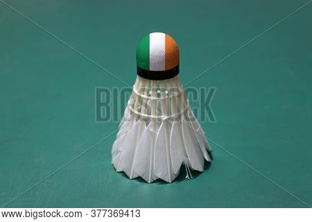 Used Shuttlecock And On Head Painted With Ireland Flag Put Vertical On Green Floor Of Badminton Cour