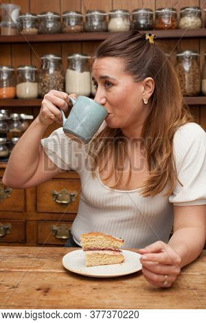 A Woman In Her 30's Drinking A Mug Of Coffee Taken 16th March 2020 In Abingdon, Oxfordshire In The U