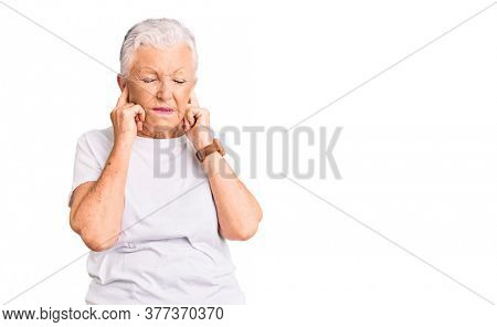 Senior beautiful woman with blue eyes and grey hair wearing casual white tshirt covering ears with fingers with annoyed expression for the noise of loud music. deaf concept.