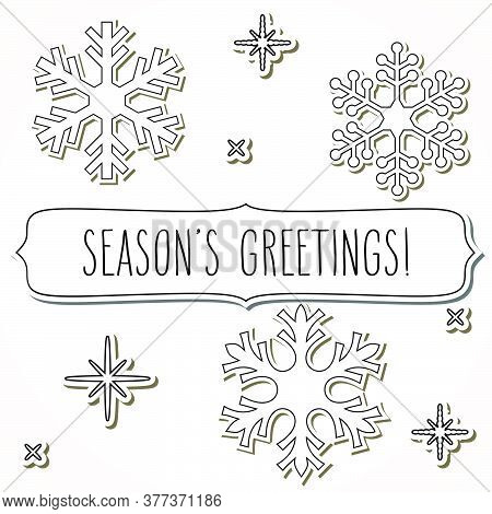 White Snowflakes And A Frame With Hand Written Season's Greetings.